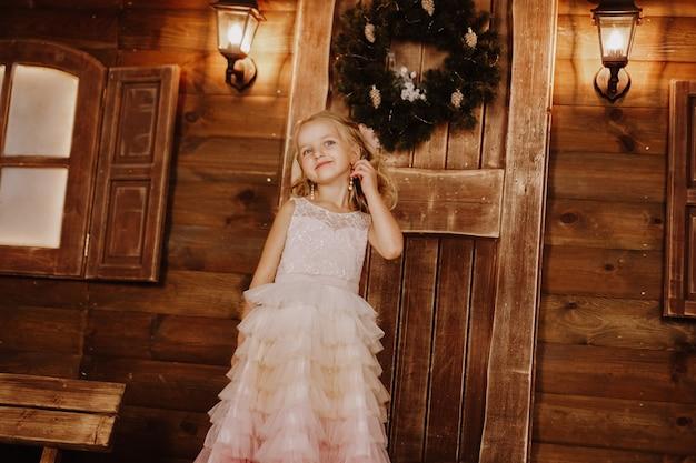 Fille aux longs cheveux blonds fixer la boucle d'oreille de perles en robe rose sur fond de bois. période de noël