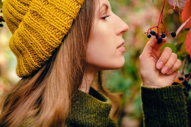 Fille aux longs cheveux bouclés en bonnet en tricot jaune moutarde et pull en laine vert marais