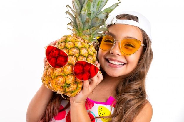 Fille aux longs cheveux crucifiés en lunettes de soleil et maillot de bain se joue avec l'ananas en lunettes de soleil