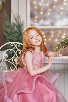 Fille aux longs cheveux roux dans une robe rose assise