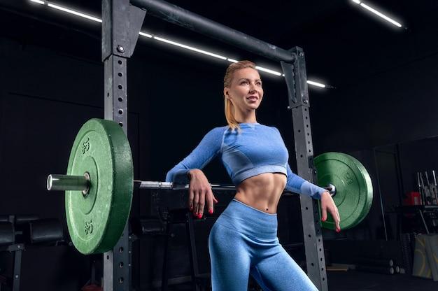 Fille aux longues jambes posant dans la salle de gym. elle s'appuya sur la barre. le concept de sport, musculation, fitness, aérobic. mode de vie sain. technique mixte