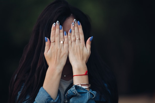 Fille aux magnifiques cheveux longs noirs se cachant le visage par les bras