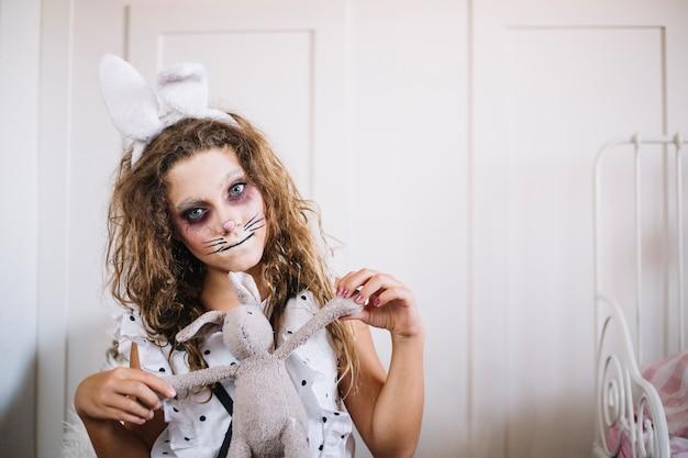 Fille aux oreilles de lapin et lapin de jouet