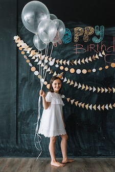 Fille aux pieds nus avec des ballons près des décorations d'anniversaire
