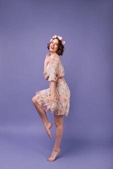 Fille aux pieds nus en tenue d'été romantique dansant. portrait en pied du modèle féminin heureux avec des fleurs dans les cheveux courts ondulés.