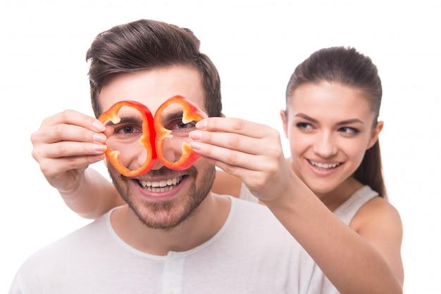 Fille aux poivrons fait des lunettes d'homme.