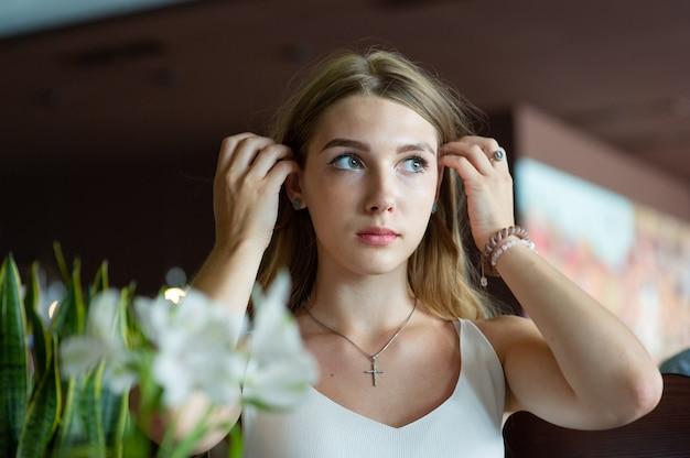 Fille aux yeux bleus assis sur un café urbain. femme avec une coiffure ondulée brune. concept de mode de vie.