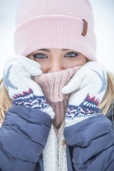 Fille aux yeux bleus blottie dans des vêtements d'hiver par une journée glaciale.
