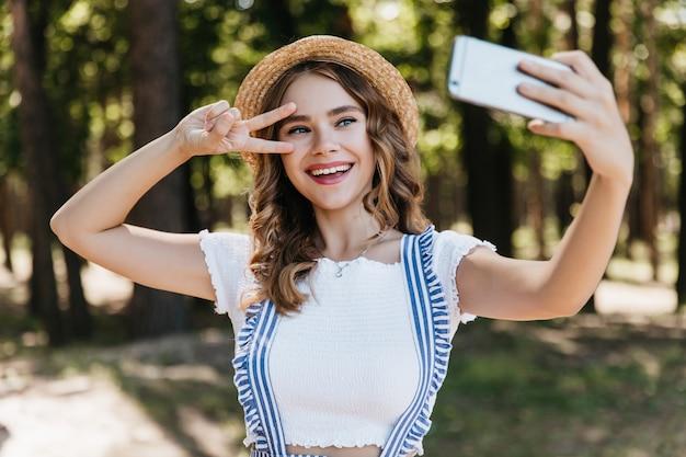Fille aux yeux bleus extatique au chapeau à l'aide de téléphone pour selfie. dame de bonne humeur aux cheveux bouclés posant avec signe de paix dans la forêt.
