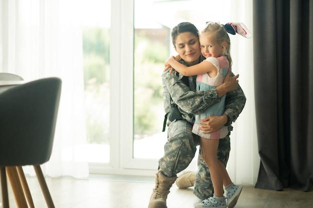 Fille aux yeux bleus. femme militaire aux cheveux noirs se sentant heureuse tout en étreignant une jolie fille aux yeux bleus