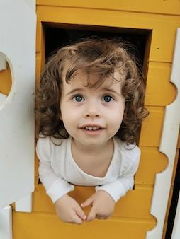 Fille aux yeux bleus jouant dans la maison de poupée.