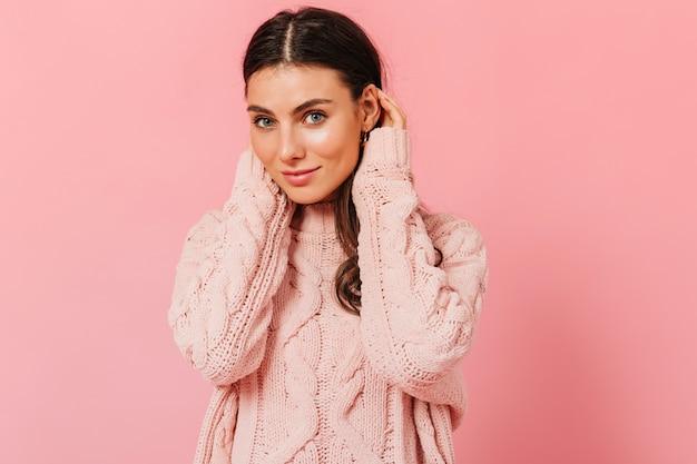 Fille aux yeux bleus sans maquillage regarde la caméra. portrait de femme en pull tricoté sur fond rose.
