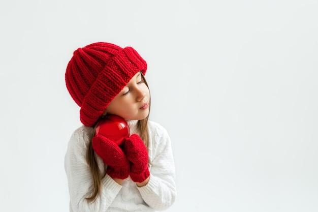 Une fille aux yeux fermés portant un bonnet et des mitaines rouges avec une boule de noël