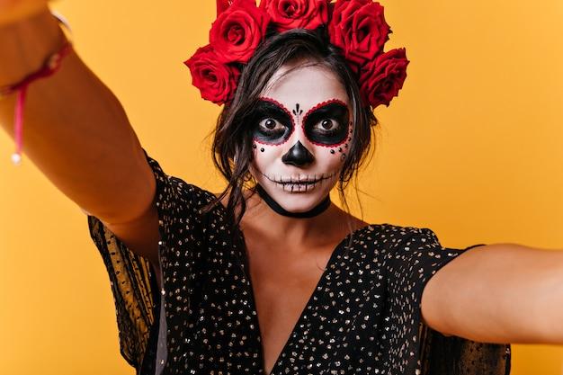 Une fille aux yeux grands ouverts de surprise fait des selfies. instantané de brune avec masque de crâne dans un mur orange