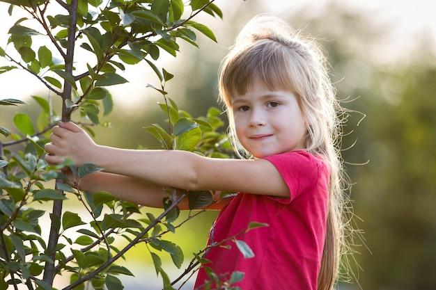 Fille aux yeux gris et longs cheveux blonds souriant timidement tenant le jeune arbre
