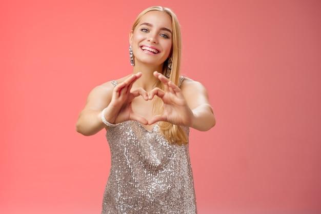 Fille avoue qu'elle t'aime. portrait charmante tendre féminine jeune femme blonde glamour en robe scintillante élégante argentée étendre la caméra des bras montrer le signe du coeur souriant largement, adorer la petite amie.