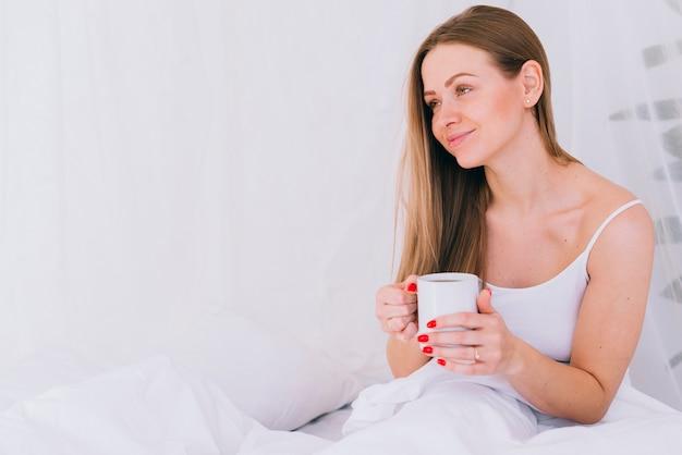 Fille ayant du café au lit