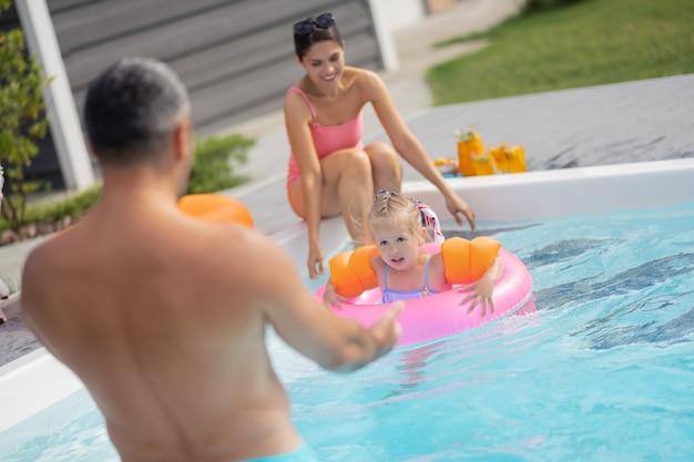 Fille ayant peur. jolie fille blonde ayant peur en nageant dans la piscine près des parents