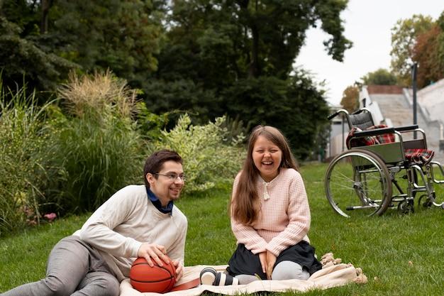 Fille ayant un pique-nique avec un homme handicapé