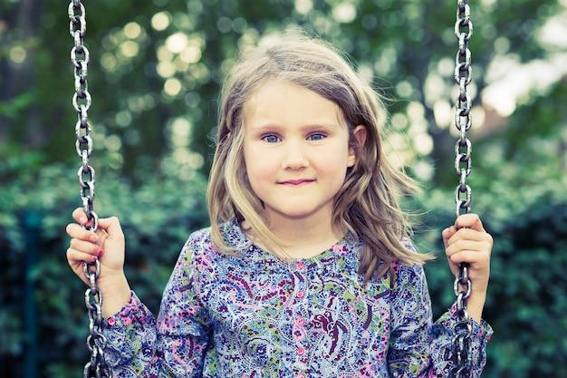 Fille sur la balançoire dans le parc d'été