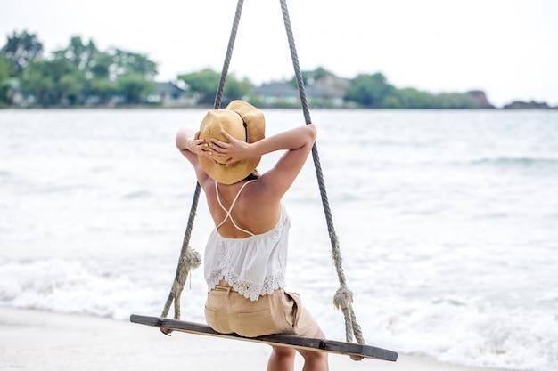 Fille sur une balançoire sur la plage de thaïlande
