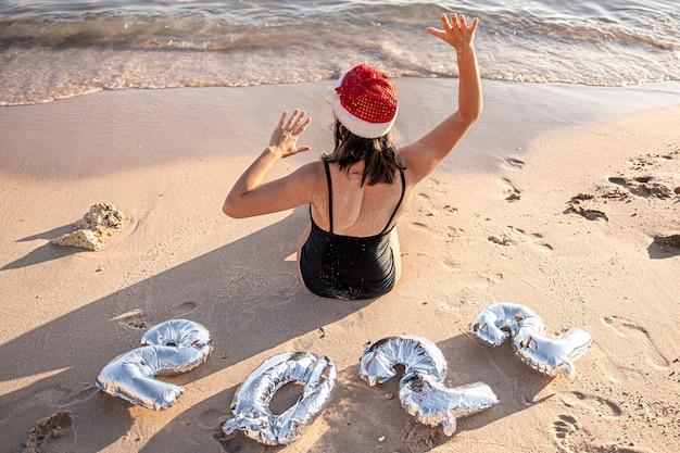 Fille avec des ballons d'argent sous forme de nombres pour l'année à venir près de la mer