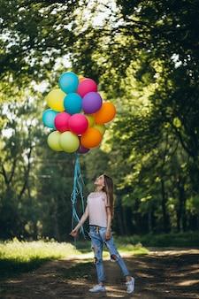 Fille avec des ballons dans le parc