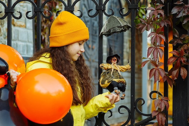 Une fille avec des ballons pour halloween joue avec une sorcière jouet dans un parc en automne