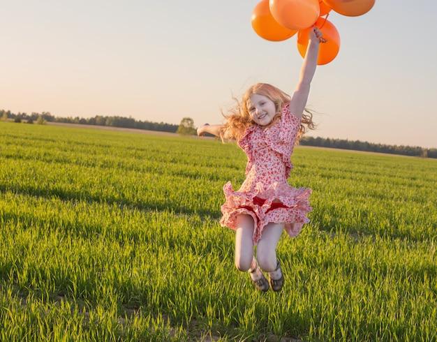 Fille avec des ballons sautant en plein air