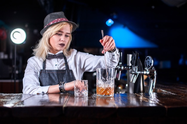 Fille barman crée un cocktail dans la brasserie