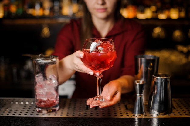 Fille de barman tenant dans les mains un verre de cocktail rouge