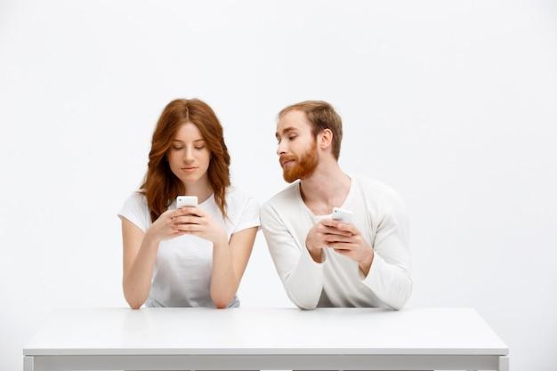 Fille bavardant, l'homme regarde son téléphone portable