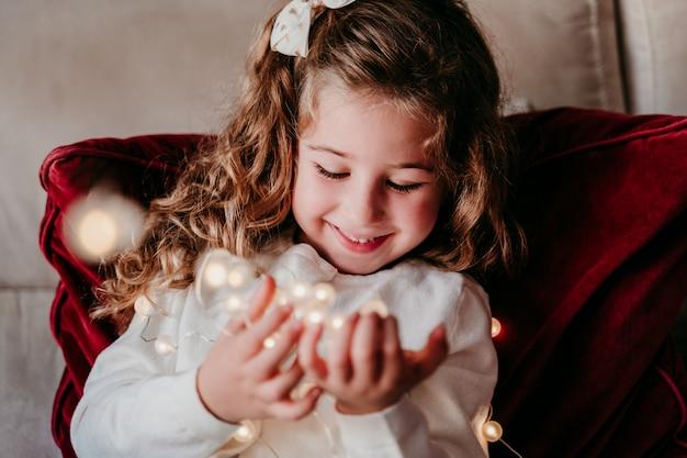 Fille de beau gosse à la maison jouant avec guirlande de lumières