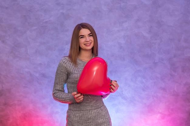 Fille de beauté avec ballon à air en forme de coeur rouge tourné en studio