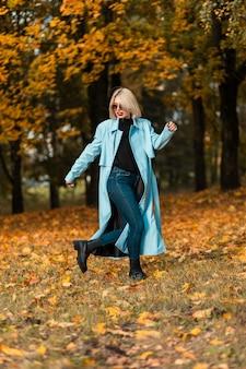 Fille de beauté de mode dans des vêtements d'automne élégants avec un manteau bleu se promène dans un parc avec des feuilles d'automne dorées.