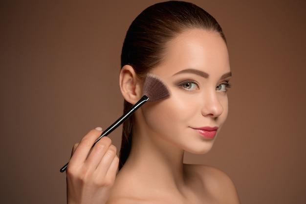 Fille de beauté avec pinceau de maquillage. peau parfaite. appliquer le maquillage