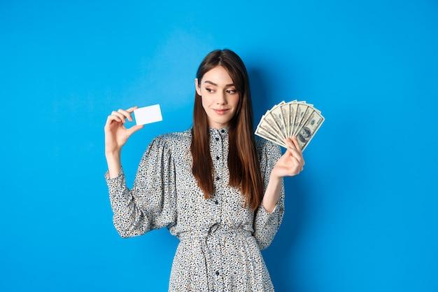 Fille de beauté en robe à la recherche de côté et souriant pensif, montrant l'argent et la carte de crédit en plastique, debout sur le bleu.