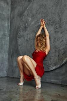 Fille de beauté sexy avec un long hiar rouge. robe rouge provocante. femme de luxe en robe élégante, mur de pierre en arrière-plan.