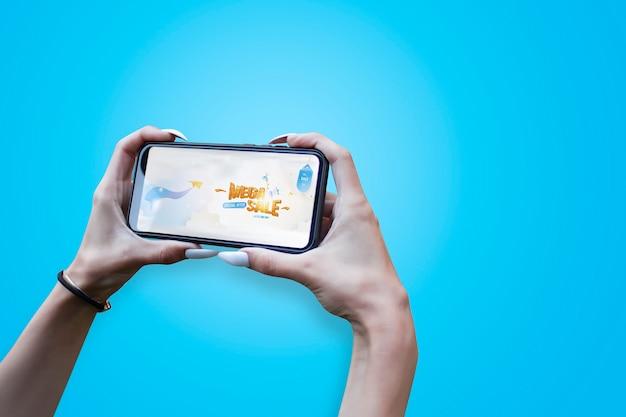 Fille avec de beaux ongles tient gros plan de smartphone avec bannière mega sale.