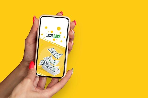Fille avec de beaux ongles tient le smartphone avec la bannière de remise en argent.