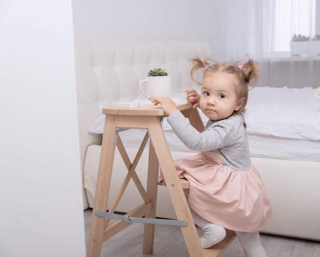 Fille de bébé drôle jouant avec des jouets à la maison dans la salle blanche.