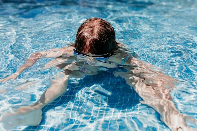 Fille belle enfant à la piscine plongée avec des lunettes de protection. amusement à l'extérieur. concept d'été et de style de vie