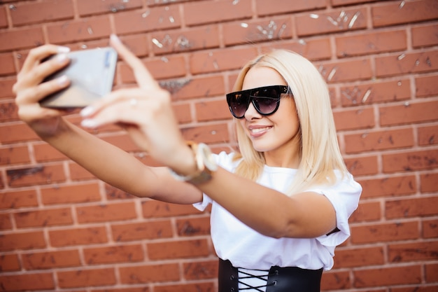 Fille de belle femme blonde prenant un selfie sur smartphone, posant debout contre le mur de briques rouges.
