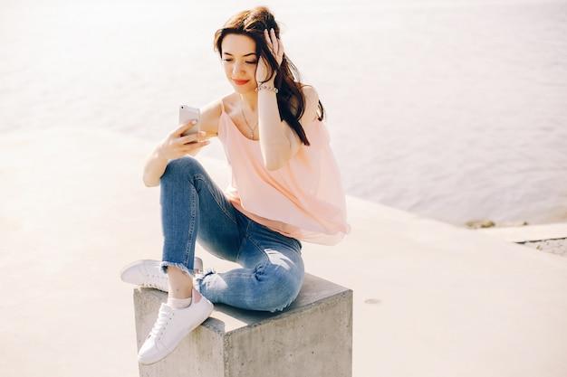 Fille belle et lumineuse en t-shirt rose et jeans bleus, assis dans le parc d'été ensoleillé