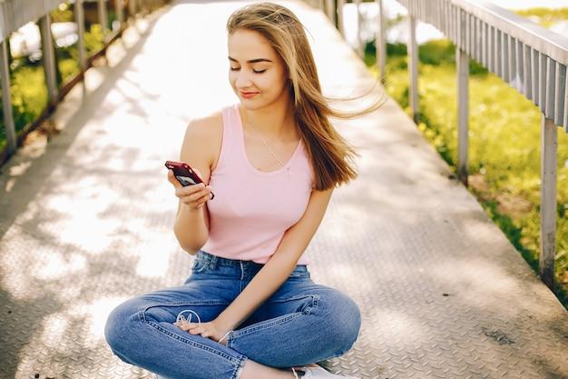 Fille belle et lumineuse en t-shirts roses et jeans bleus, assis dans le parc d'été ensoleillé