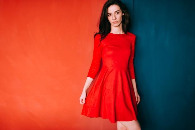 Fille belle mode avec des cheveux longs noirs et un visage sensuel en robe élégante rouge posant sur un mur rouge bleu. portrait de mode de vie intérieur d'une femme élégante.
