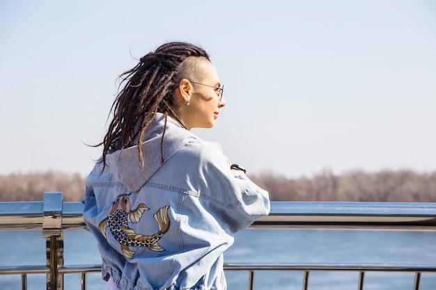 Fille belle à la mode moderne seule sur une promenade de printemps au bord de la rivière