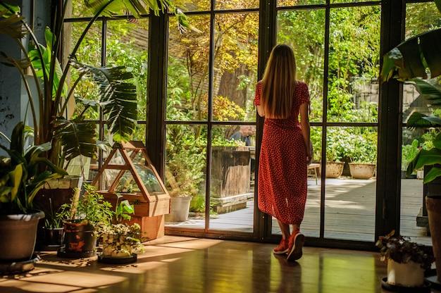 Fille en belle robe rouge en regardant la fenêtre