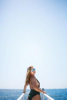 Une fille avec une belle silhouette dans un maillot de bain vert. elle est sur un yacht blanc dans la mer rouge