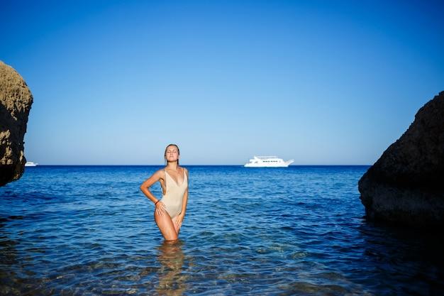 Une fille avec une belle silhouette en maillot de bain beige dans l'eau bleue de la mer rouge. elle se tient sous le soleil éclatant